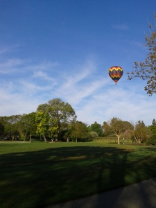 Hot air balloon over village green